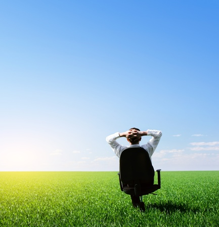 green office: Businessman sitting on chair in green meadow and looking to a blue clear sky