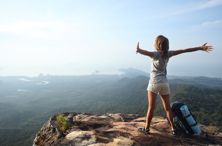 adventure sports: Young woman with backpack standing on cliffs edge and looking to a sky with raised hands