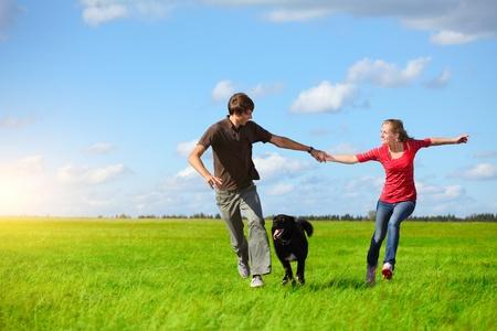 Joven pareja feliz que se ejecutan en pradera verde con un perro
