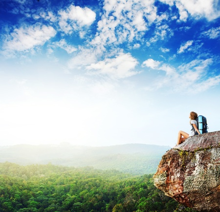 mountain top: Young woman with backpack sitting on cliff and looking to a sky Stock Photo