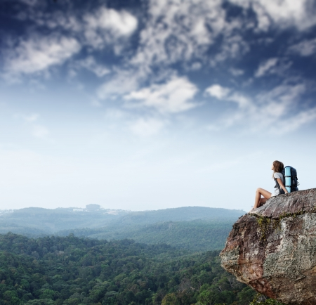 trekker: Young woman with backpack sitting on cliff and looking to a sky Stock Photo