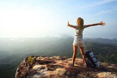 Young woman with backpack standing on cliffs edge and looking to a sky with raised hands photo