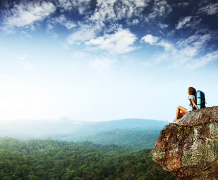 Young woman with backpack sitting on cliff and looking to a sky Фото со стока