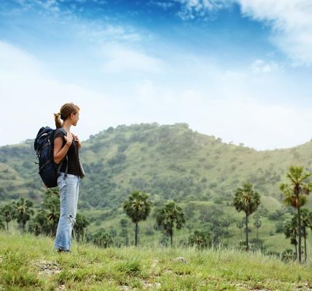 崖の端に立っているとどこかに探しているバックパックを持つ若い女