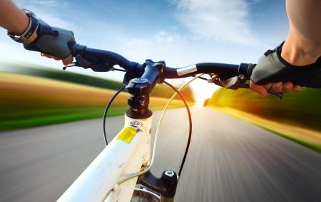 ciclismo: Manos en guantes con el manillar de una bicicleta. Carretera de asfalto borrosa de movimiento