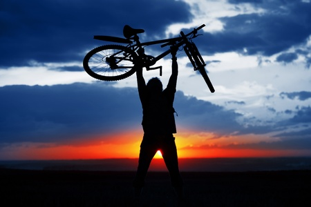 Man holding a bicycle over himself on sunset background Stock Photo