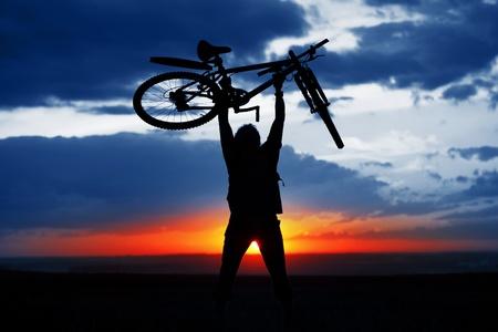 Mann, der ein Fahrrad über sich selbst auf sunset Hintergrund hält Standard-Bild