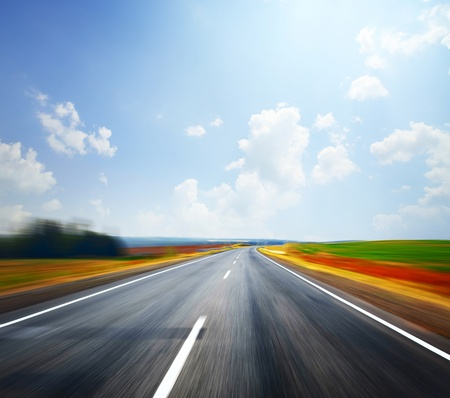 Asphalt blurry road and bright blue sky with clouds photo