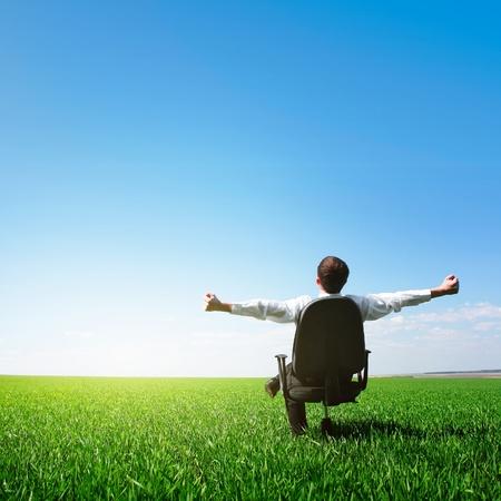 manos levantadas al cielo: Hombre sentado en silla en pradera verde sobre fondo azul cielo claro