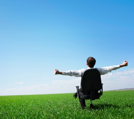 Man sitting on chair on green meadow on blue clear sky background photo