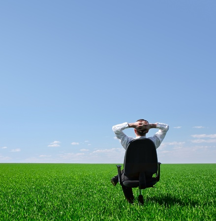 Man sitting on chair on green meadow on blue clear sky background Stock Photo - 9266106