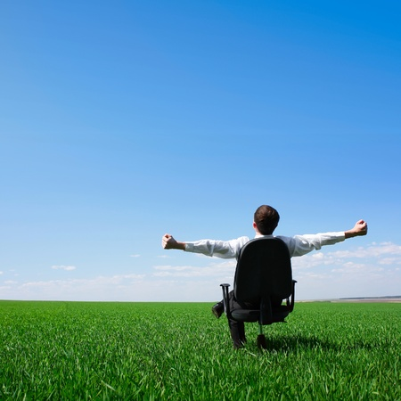 tilt views: Man sitting on chair on green meadow on blue clear sky background