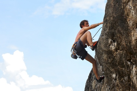 kletterer: Junges M�nnchen Klettern auf einer Klippe auf blau bew�lkten Himmel Hintergrund