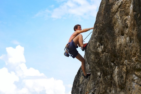 tenacity: Young male climbing on a cliff on blue cloudy sky background