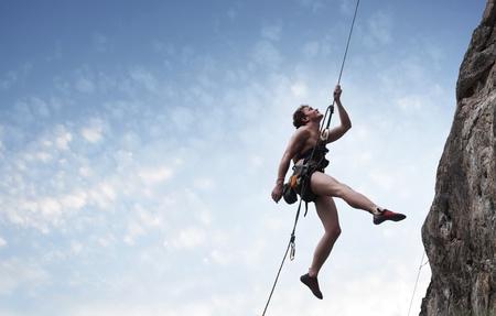 mountain climber: Giovane maschio scalatore appesa a un filo e cercando di da qualche parte su sfondo blu cielo nuvoloso