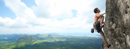 mountain climber: Giovane maschio arrampicata su una scogliera su sfondo di ampia vicolo