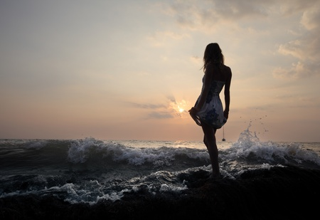 Young woman standing on a rock in sea and holding her dress. photo