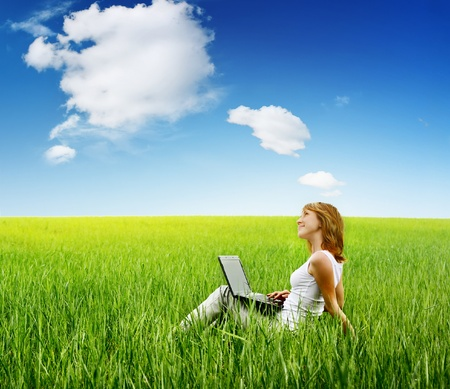 think green: Young woman sitting with laptop on green grass and looking to a sky. Stock Photo