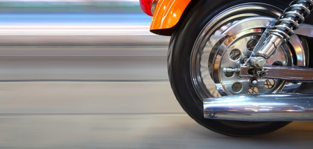 Part of a modern motorcycle with blurred road and wheels photo