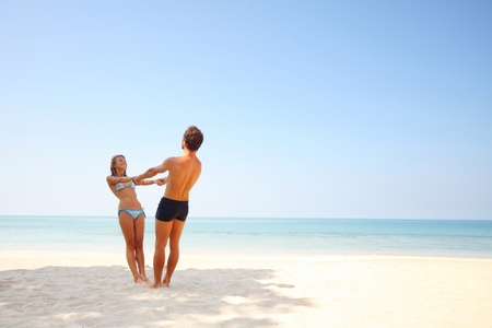 Young lovers standing on warm sand at sunny day and enjoying each other photo