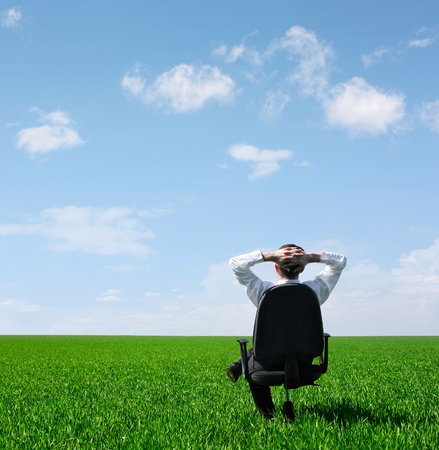Man sitting on chair on green meadow on blue cloudy sky background Stock Photo - 9266222
