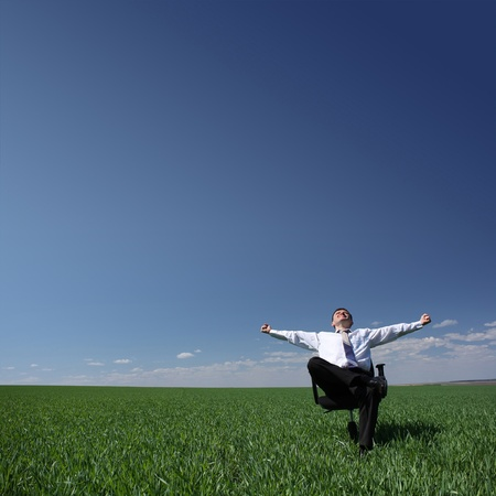 enjoy space: Man sitting on chair on green meadow on blue clear sky background