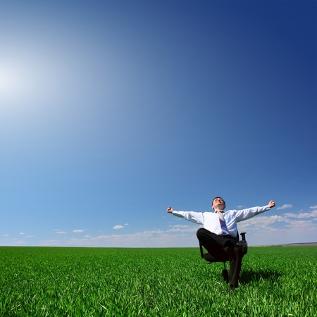 Man sitting on chair on green meadow on blue clear sky background Stock Photo - 9266221