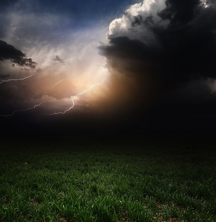 horizon over land: Dark storm clouds with flashes over meadow with green grass Stock Photo