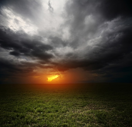 Dark storm clouds over meadow with green grass Stock Photo - 9266724