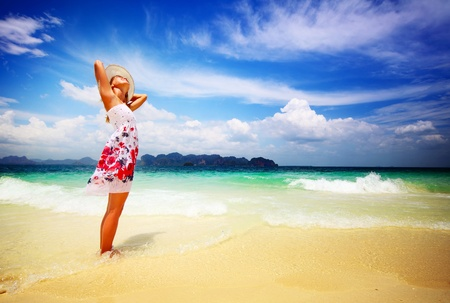 Young woman in summer dress standing on sand and holding straw hat looking to a sky Stock Photo - 9266109