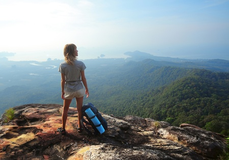 Young woman with backpack standing on cliff's edge and looking to a sky Stock Photo - 9266220