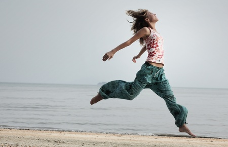 Young smiling woman running and jumping on a beach photo