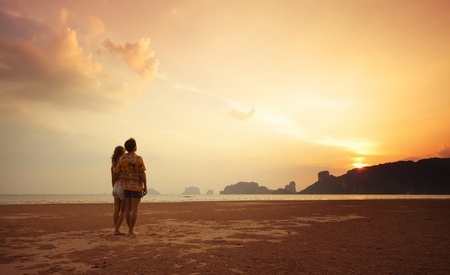 Two young lovers standing on beach and looking to a sun photo