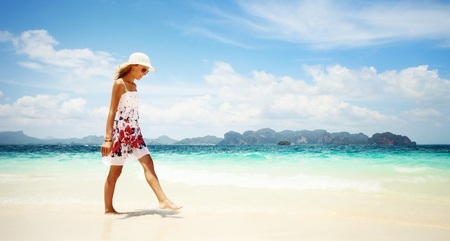 Young woman in dress and straw hat walking on beach Stock Photo