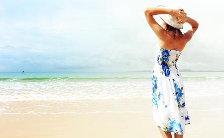 海の近くの砂の上に立っていると、帽子を保持しているドレスの若い女性