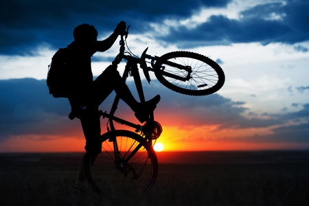 gimmick: Man doing bycycle juggle on sunset background