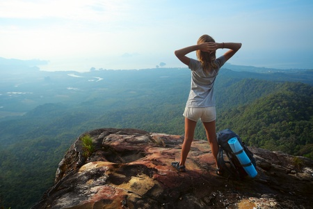trek: Young woman with backpack standing on cliffs edge and looking to a sky Stock Photo