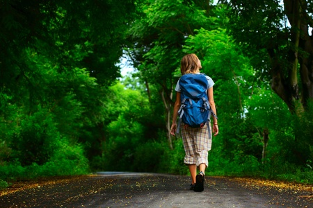 long feet: Young woman with backpack walking on a wet asphalt path in a park