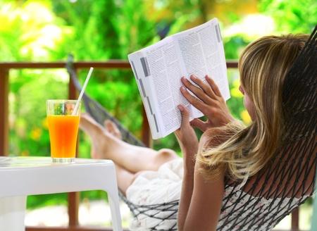 hamac: Jeune femme allong� dans un hamac en jardin vert et un livre de lecture