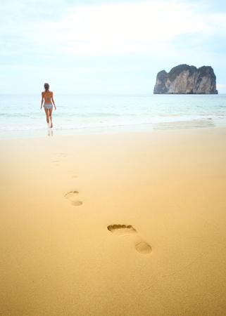 cuerpo femenino perfecto: Joven caminando sobre mojado arena perfecto y va a nadar en un mar