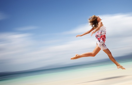 Young woman in summer dress jumping on sand. Motion blurred background
