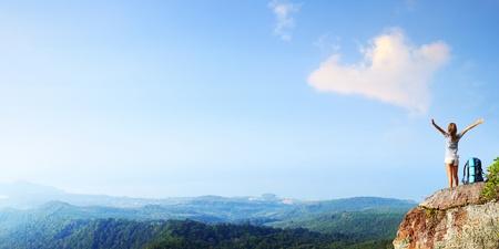 manos levantadas al cielo: Mujer joven con mochila de pie en el borde del precipicio con manos alzadas y mirando a un cielo Foto de archivo