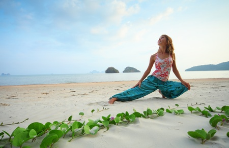 inclination: Young smiling woman doing exercises on sand on blue sky backgound Stock Photo