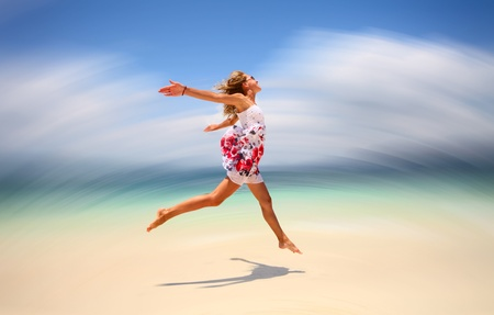 Young woman in summer dress jumping on sand. Motion blurred background photo