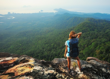 freedom leisure activity: Young woman with backpack standing on cliffs edge and looking to a sky Stock Photo