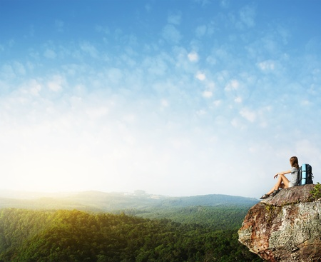 cliff top: Young woman with backpack sitting on cliffs edge with raised hands and looking to a sky Stock Photo