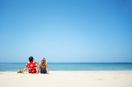 Young lovers sitting on warm sand at sunny day and looking to somewhere photo