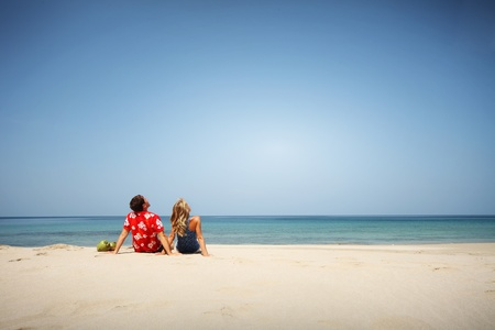 honeymoon couple: Young lovers sitting on warm sand at sunny day and looking to somewhere Stock Photo