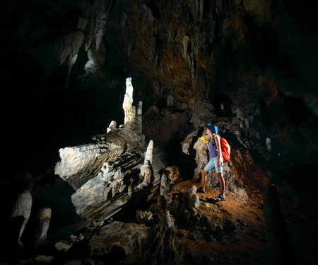 caving: Young woman with backpack exploring huge cave with torch