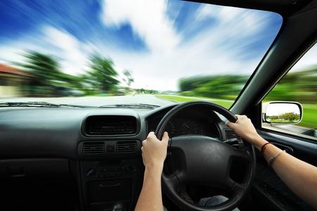conducci�n: Manos en el volante de un coche y la carretera de asfalto borrosa de movimiento y el cielo